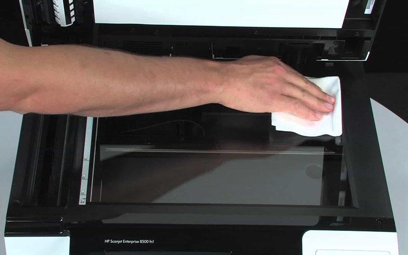 Sử dụng vải mềm để vệ sinh gương phản xạ máy photocopy